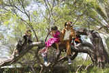 Children in costume climbing in tree