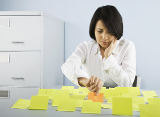 Businesswoman choosing one adhesive note from many