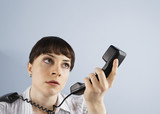 Frustrated businesswoman looking at telephone handset