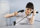 Businesswoman tangled in telephone cords