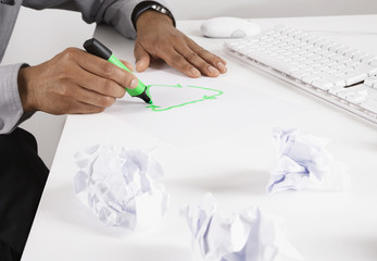Businessman drawing recycling symbol on desk with marker