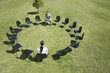 Business people sitting in circle of office chairs in field