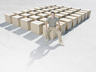 Man sitting on line of boxes