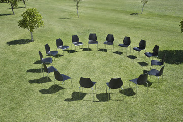 Office chairs in a circle in field