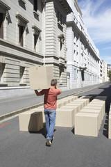 Man carrying box on urban street
