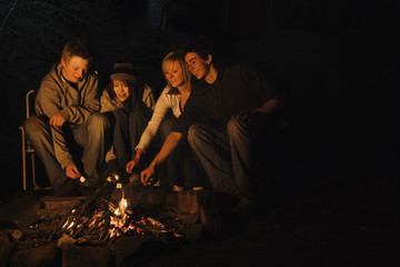 Teenage couples roasting marshmallows over campfire