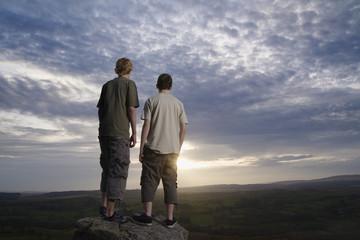 Teenage boys on rock viewing countryside