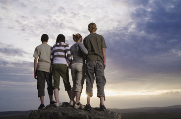 Teenage friends standing on rock viewing countryside