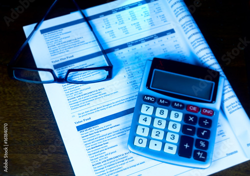 Evaluating the 401k with calculator and eyeglasses.