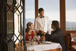 Waiter serving couple in elegant restaurant