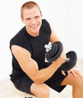 Happy young man exercising with a dumbbell