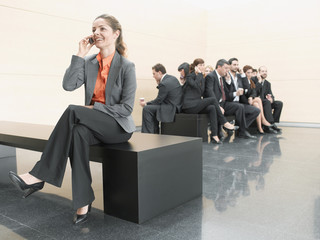 Businesswoman using cell phone away from co-workers