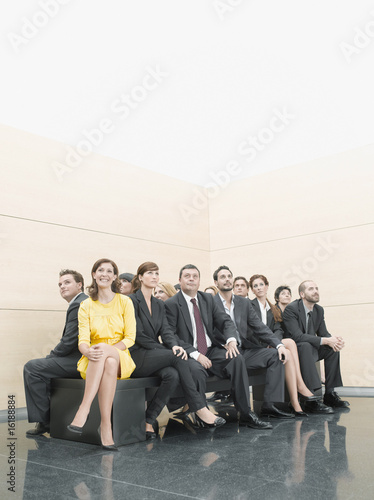 Businesspeople sitting on crowded office bench