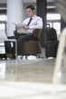 Businessman waiting with luggage in hotel lobby