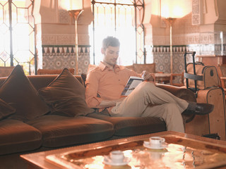 Man reading in hotel lobby