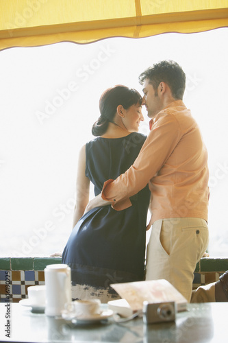 Romantic couple hugging in outdoor cafe