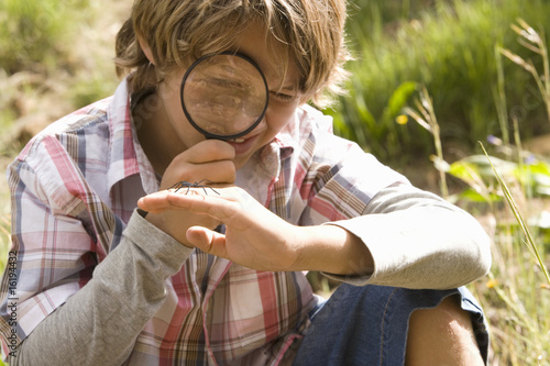 Boy looking at insect through magnifying glass