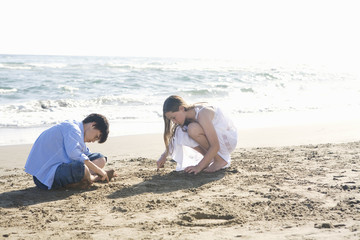 Friends drawing in sand on beach