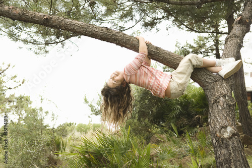 Girl hanging from tree branch