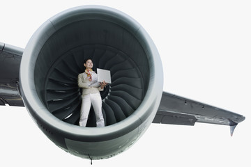 Businesswoman standing in airplane engine