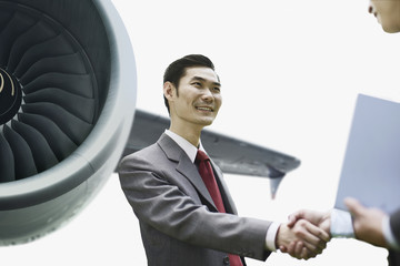 Businessmen shaking hands by airplane