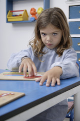 Girl playing with puzzle in school