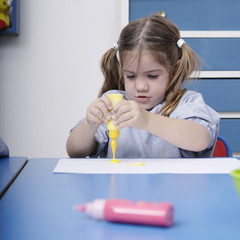 Girl finger-painting in classroom