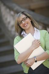 Businesswoman clutching laptop