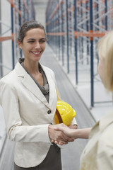 Businesswoman shaking hands in warehouse