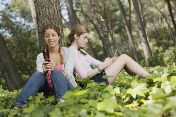 Girls text messaging in forest
