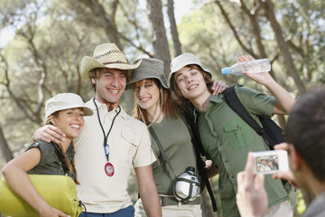 Friends posing for photograph in forest