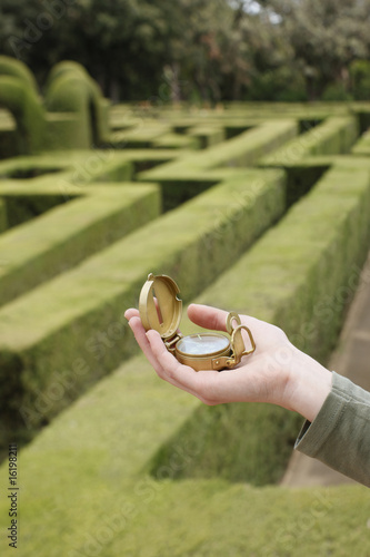 Woman holding compass in hedge maze