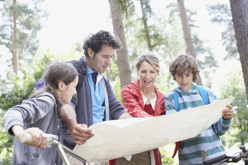 Family looking at map in woods