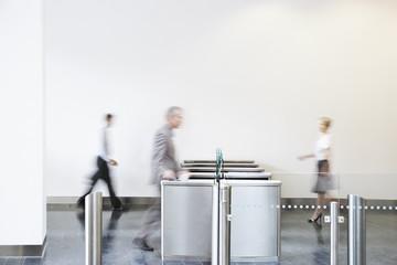 Businesspeople walking through turnstile