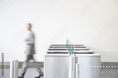 Businessman walking through turnstile
