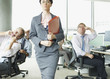 Businesspeople making face at boss in office