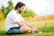 Young man is laying on green ground with laptop