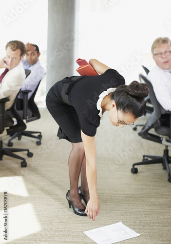Businesswoman picking papers up from floor