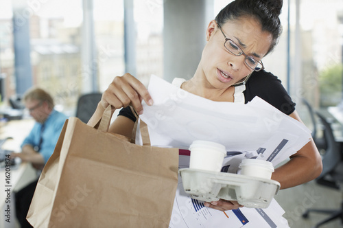 Frustrated businesswoman talking on cell phone with paperwork and coffee