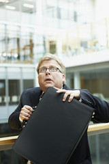 Afraid businessman holding briefcase