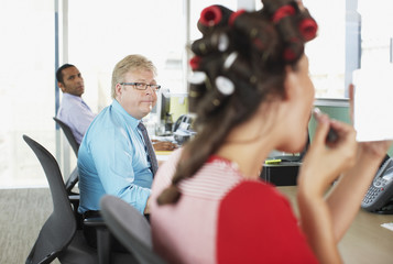 Businesswoman in curlers putting on lipstick in office