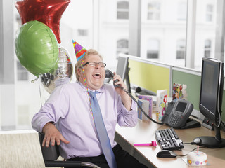 Laughing businessman having birthday party at desk