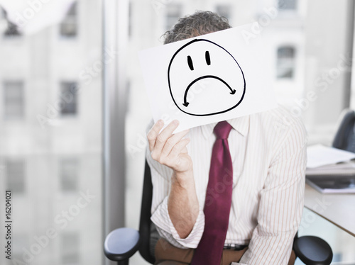 Businessman holding picture of sad face