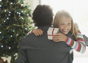Daughter hugging father holding Christmas gift