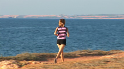 The young woman plays sports against the sea. She runs