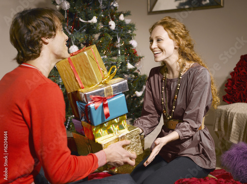 Man giving wife pile of Christmas gifts