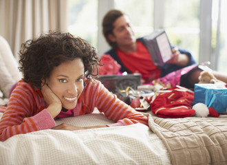 Couple laying on bed with Christmas gifts