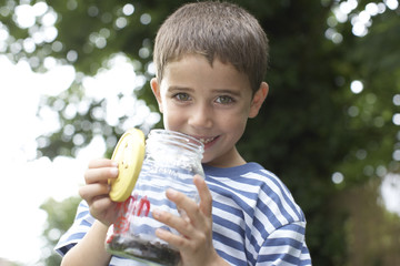 Boy holding insect jar