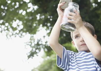 Boy looking at insect jar