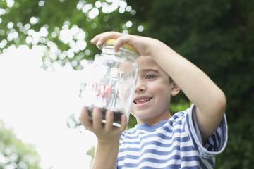 Boy looking at insect jar